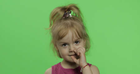 Child portrait in purple dress. Nose picking. Happy four years old girl. Pretty little blonde child. Make faces and smile. Place for your logo or text. Green screen. Chroma Key Foto de archivo
