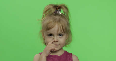 Child portrait in purple dress. Nose picking. Happy four years old girl. Pretty little blonde child. Make faces and smile. Place for your logo or text. Green screen. Chroma Key