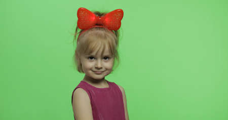 Positive girl in purple dress and red ribbon on head looking at camera. Pretty little blonde child. Make faces and smile. Place for your logo or text. Green screen. Chroma Key 스톡 콘텐츠