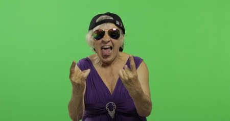 An elderly woman shouts with a smile and showing tongue. Old pretty happy grandmother in sunglasses and cap. Place for your logo or text. Chroma key. Green screen background
