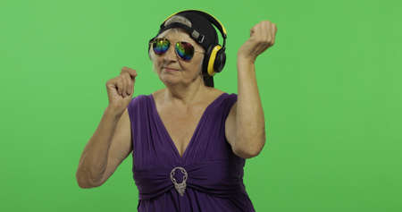 An elderly woman listens to music in headphones and dances. Old pretty happy grandmother in sunglasses and cap. Place for your logo or text. Chroma key. Green screen background