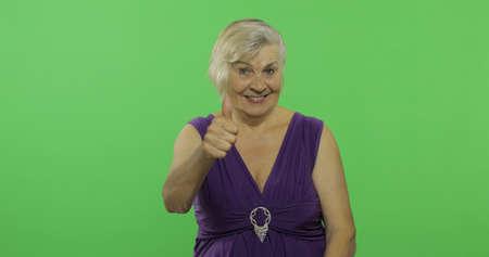 Una anciana muestra el pulgar hacia arriba y sonríe. Abuela bonita con un vestido morado. Lugar para su logo o texto. Clave de croma. Fondo de pantalla verde