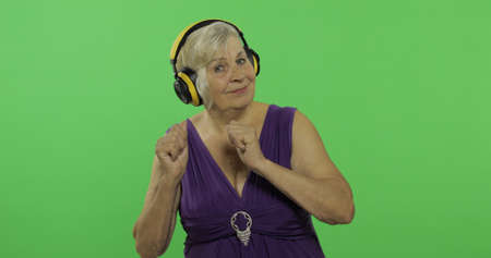An elderly woman listens to music in headphones and dances. Old pretty grandmother in a purple dress. Place for your logo or text. Chroma key. Green screen background