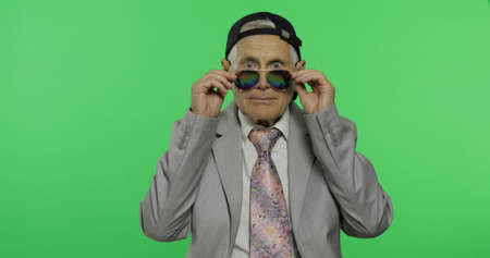 Funny elderly businessman in sunglasses and cap. Old man in formal wear winks on chroma key background. Place for your logo or text. Green screen background 版權商用圖片
