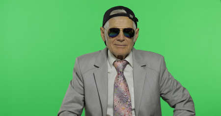 Funny elderly businessman in sunglasses and cap smiles. Old man in formal wear winks on chroma key background. Place for your logo or text. Green screen background