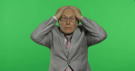 Elderly businessman. Desperate worried. Stressed shocked old senior man in formal wear holding head with hands on chroma key background. Place for your logo or text. Crisis in business concept