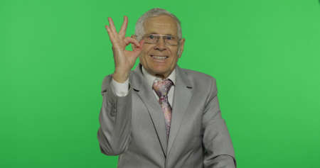 Elderly businessman showing ok gesture. Old man in formal wear giving okay sign on chroma key background. Symbol of agreement and success. Green screen background 版權商用圖片