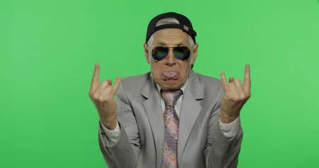 Funny elderly businessman in sunglasses and cap show sign of the horns with his hands. Old man in formal wear on chroma key background. Place for your logo or text. Green screen background