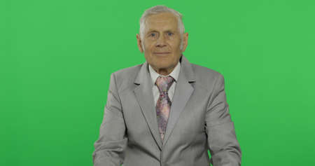 Elderly businessman looking to camera. Old man in formal wear on chroma key background. Place for your logo or text. Green screen background Imagens