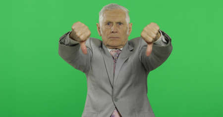 Elderly businessman giving thumb down. Old man in formal wear showing thumb down gesture on chroma key background. Symbol of unagreement and fail. Green screen background