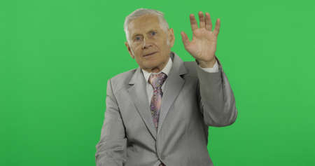 Elderly businessman waving with hand to camera. Old man in formal wear on chroma key background. Place for your logo or text. Green screen background