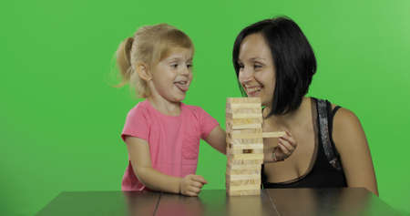 Woman and child plays . A little child pulls wooden blocks from tower. Block removal game. Happy family. Mother and daughter. Chroma key background