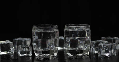 Shots of vodka with ice cubes against black background. Alcohol drink vodka tequila