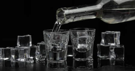 Pouring up shots of vodka from a bottle into drinking glass against black background with ice cubes. Pour of alcohol drink vodka tequila