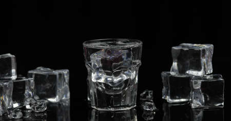 Shot of vodka with ice cubes against black background. Alcohol drink vodka tequila