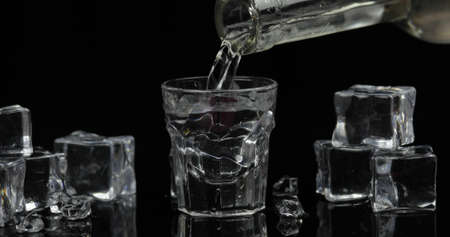 Pouring up shot of vodka from a bottle into drinking glass against black background with ice cubes. Pour of alcohol drink vodka tequila
