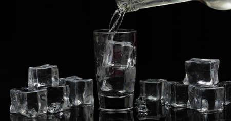 Schuss Wodka aus einer Flasche in ein Trinkglas vor schwarzem Hintergrund mit Eiswürfeln gießen. Gießen Sie Alkohol trinken Wodka Tequila