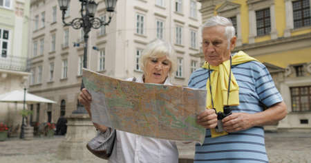 Senior two male and female tourists standing in town with a map in hands and looking for the route while traveling in Lviv, Ukraine. Elegant woman in hat. A man with binoculars. Vacation concept
