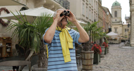 Senior male tourist exploring town while traveling in Lviv, Ukraine. Looks in binoculars. T-shirt and sweater in his neck. Vacation concept