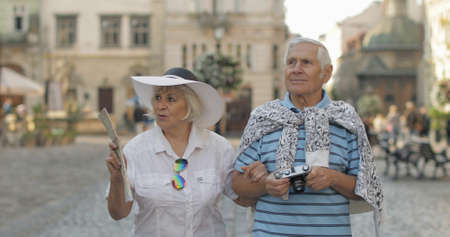 Senior two male and female tourists walking in town center. Traveling in Lviv, Ukraine. Elegant woman in hat with map in her hand. Handsome man with photo camera. Family vacation concept Фото со стока