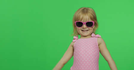 Child in pink swimsuit and sunglasses. Happy, pretty little blonde girl, 3-4 years old. Make faces and smile. Summer vacation concept. Green screen. Chroma Key