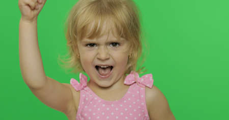 Girl emotionally make faces and show anger in pink swimsuit. Portrait close up. Angry, cute little blonde child, 3-4 years old. Green screen. Chroma Key