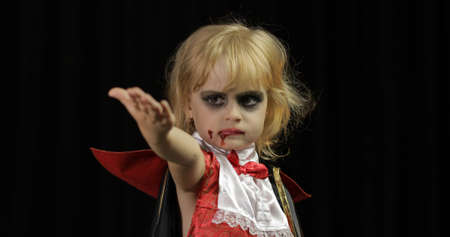 Dracula child. Little girl with halloween make-up making faces. Vampire kid with blood on her face. Happy Halloween holiday horror concept. Friday 13th theme