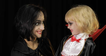 Woman and child dracula making faces. Little girl with her mother. Halloween make-up. Vampire kid with blood on her face. Happy Halloween holiday horror concept. Friday 13th theme