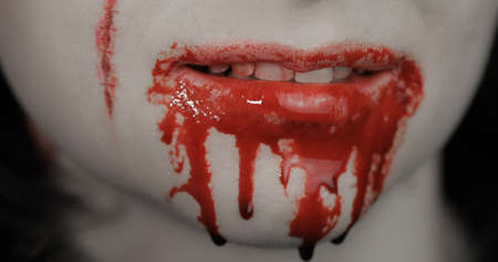 Bloody mouth and teeth of girl. Vampire woman Halloween makeup with dripping blood. Friday 13th theme Фото со стока - 129837774