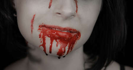Bloody mouth and teeth of girl. Vampire woman Halloween makeup with dripping blood. Friday 13th theme
