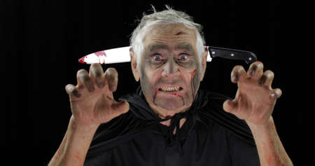 Elderly man with knife in head. Halloween makeup and costume. Old man with dripping blood on his face. Fashion art design. Attractive model in Halloween costume. Black background 写真素材
