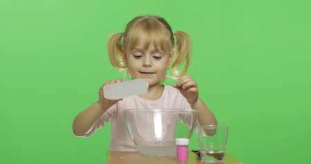 Child having fun making slime. Pour the glue. Kid playing with hand made toy slime. Funny kid girl. Oddly satisfying slime for pure fun and stress relief. Dark background