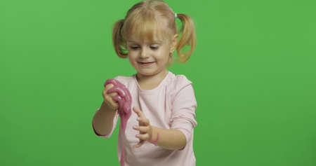 Child having fun making ping slime. Kid playing with hand made toy slime. Funny kid girl. Relax and Satisfaction. Oddly satisfying pink slime for pure fun and stress relief. Green screen. Chroma Key