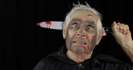 Elderly man with knife in head. Halloween makeup and costume. Old man with dripping blood on his face. Fashion art design. Attractive model in Halloween costume. Black background Stok Fotoğraf