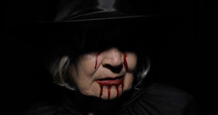 Old witch Halloween woman portrait. Elderly vampire woman with dripping blood on her mouth and eyes. Witch makeup. Fashion art design. Attractive model in Halloween costume. Black background