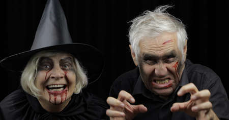 Elderly man and woman in Halloween costumes. Dripping blood on their faces. Witch, vampire, zombie makeup. Fashion art design. Attractive models. Black background 版權商用圖片