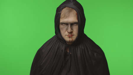 Executioner Halloween man portrait. Guy with dripping blood on his face. Executioner, headman makeup. Fashion art design. Attractive model in Halloween costume. Chroma key background
