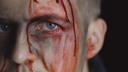 Portrait d'homme Halloween avec une blessure à la tête. Guy avec du sang dégoulinant sur son visage. Gros plan sur son œil ensanglanté. L'homme après le maquillage de combat. Modèle attrayant à Halloween. Fond noir foncé