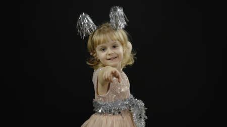 Happy beautiful little baby girl in glossy dress emotionally points at something with her hands. Christmas concept. Positive, pretty, four years old child make faces and smile. Black background