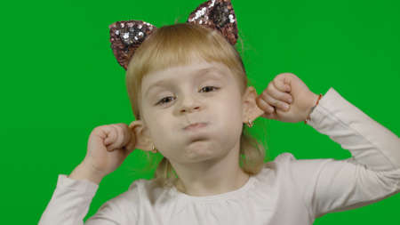 Girl in cat headband touches her ears and make faces. Happy four years old girl. Pretty little blonde child. Green screen. Chroma Key