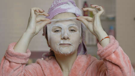 Woman applying cosmetic face mask and looking at camera in bathroom. Girl taking care of her face skin. Skincare spa treatment. Facial mask Imagens