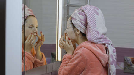 Woman applying cosmetic face mask and looking at mirror in bathroom. Girl taking care of her face skin. Skincare spa treatment. Facial mask Standard-Bild