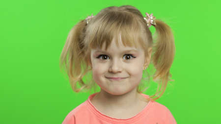 Positive happy girl smiles in pink blouse with stars. Portrait close up. Happy, cute little blonde child, 4-5 years old. Green screen. Chroma Key. Place for your logo or text Banque d'images