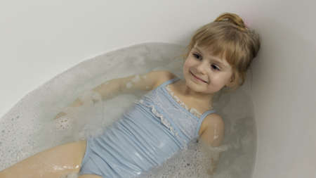 Attractive four years old girl takes a bath in swimwear. Hygiene for cute blonde child. Cute girl smiling. Pretty little child, 4-5 year old blonde girl in bathroom
