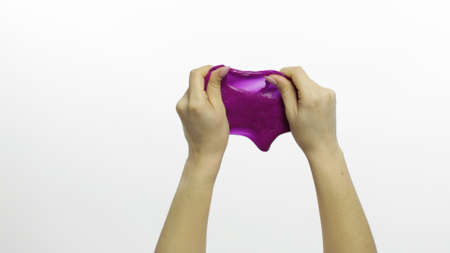 Woman hands playing with oddly satisfying purple slime on white background. Sticky gooey substance. Relax and inexplicably satisfying. Super viral trend on social media for antistress things