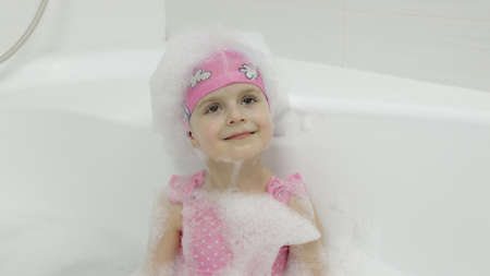 Attractive four years old girl takes a bath with bath foam in pink swimwear and swimming cap. Bath foam on head. Hygiene for cute blonde child. Cute girl smiling. Little blonde child girl in bathroom