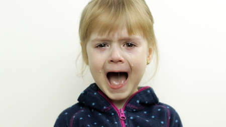 Portrait of little toddler girl crying with mouth wide open and tears down her face isolated on white background. Childhood concept. Studio shot of child emotions. Close up Imagens