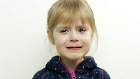 Portrait of little toddler girl crying and tears down her face. Isolated on white background. Childhood concept. Studio video of child emotions. Close up. Blonde child, 4-5 years old
