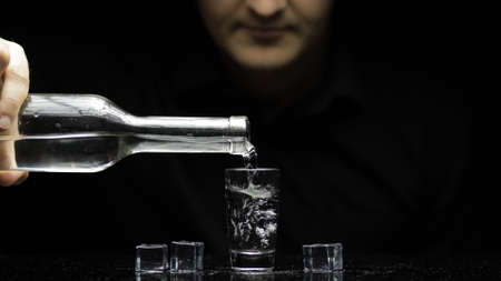Bartender pouring up frozen vodka from a bottle into shot glass with ice cubes against black background. Barman pour of clear transparent alcohol drink vodka tequila in shot-glass. Concept alcoholism Stok Fotoğraf