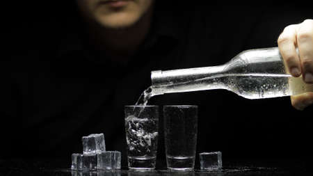 Bartender pouring up frozen vodka from a bottle into two shots glasses with ice cubes against black background. Barman pour of clear transparent alcohol drink rum tequila in shot-glass Stok Fotoğraf